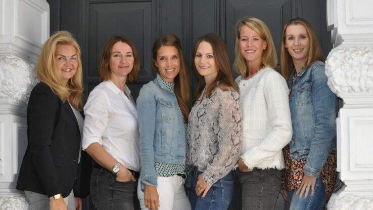 Fotografie von sechs Frauen vor einer Tür.