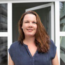 Portraitfotografie Anne Heitkämper mit geöffneter Glastür im Hintergrund.
