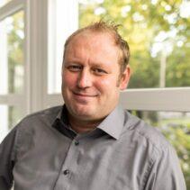 Dennis Nothaft Portraitfotografie vor Fensterfront mit grünen Bäumen im Hintergrund..
