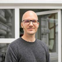 Portraitfotografie Simon Brunke mit geöffneter Glastür im Hintergrund.