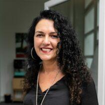 Portraitfotografie Vera Stünkel mit geöffneter Glastür im Hintergrund.
