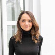 Portrait Alexandra Sophie Fritz vor geöffneter Glastür.