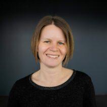Portrait Julia Windeck vor schwarzem Hintergrund.
