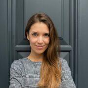 Portrait Kathrin Stolze vor grauer Tür.