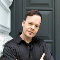 Oliver Clausen Portrait vor grauer NDR Media Eingangstür.