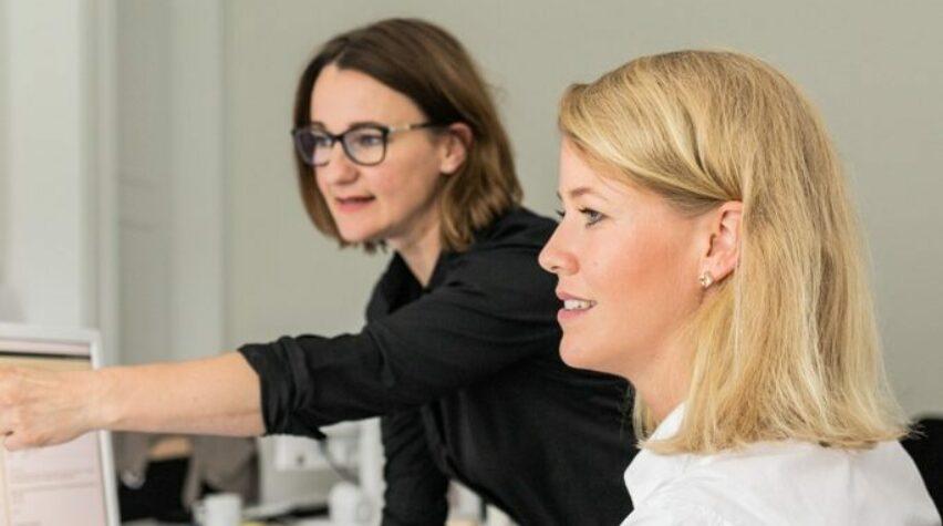 Zwei Frauen schauen auf einen Computerbildschirm.