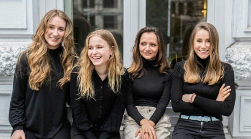 Vier Frauen sitzen auf einem Fensterbrett und lachen.