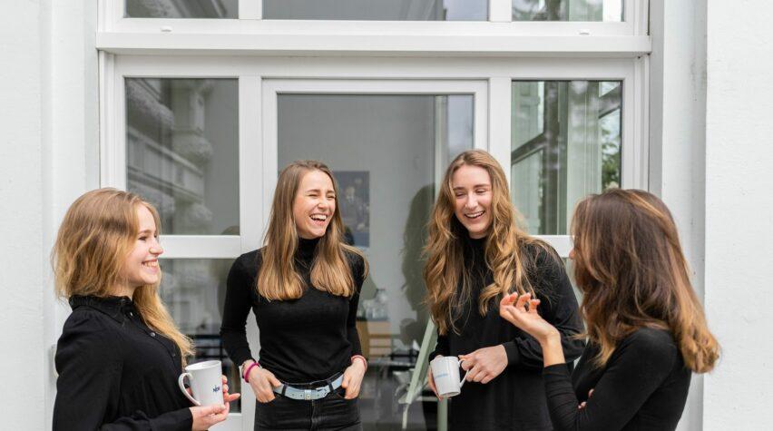 Fotografie junger Frauen lachend mit Kaffeetassen in der Hand.
