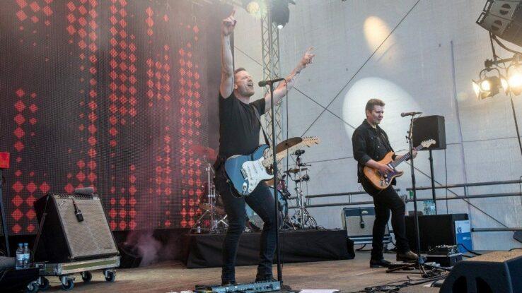 Zwei Musiker auf der Bühne mit Gitarren.