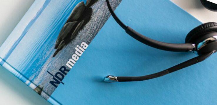 Fotografie eines schwarzen Headsets auf NDR Media Buch.