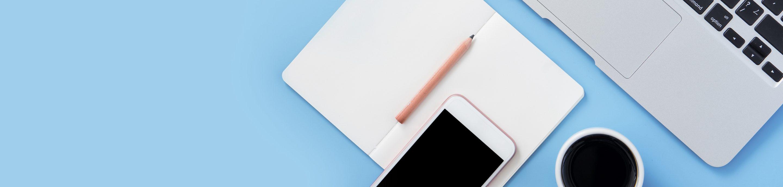 Aufsicht auf Mobiltelefon, Notizbuch, Stift und Laptop.