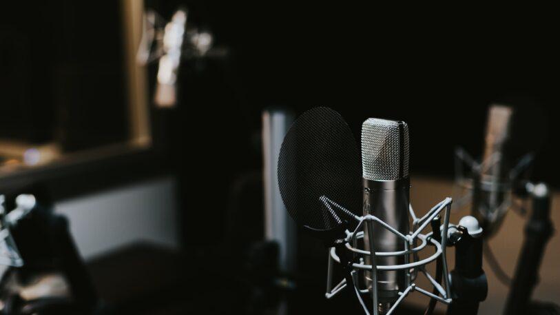Fotografie eines Mikrofons im dunklen Raum eines Studios.