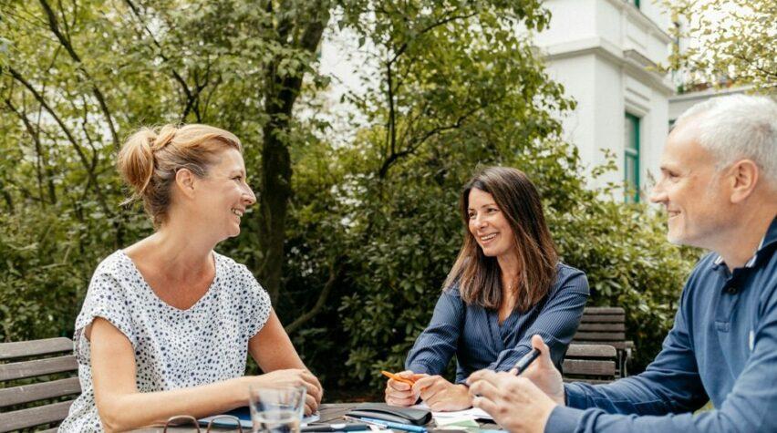 Fotografie einer Unterhaltung von zwei lachenden Frauen und eines Mannes im Garten am Tisch mit Unterlagen.