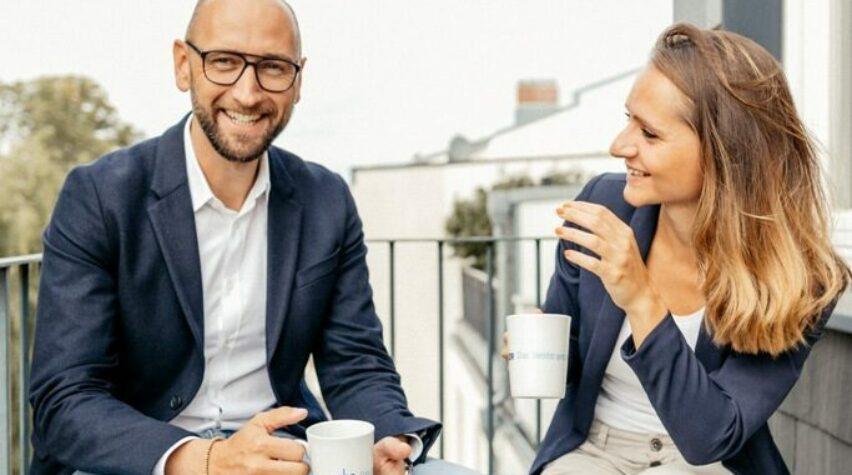 Fotografie einer Frau und eines Mannes mit Kaffeetassen in der Hand auf einer Bank auf dem Balkon sitzend.