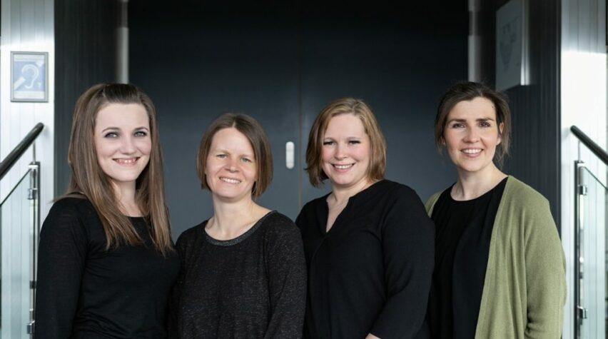 Fotografie von vier Frauen, die seitlich in die Kamera schauen.
