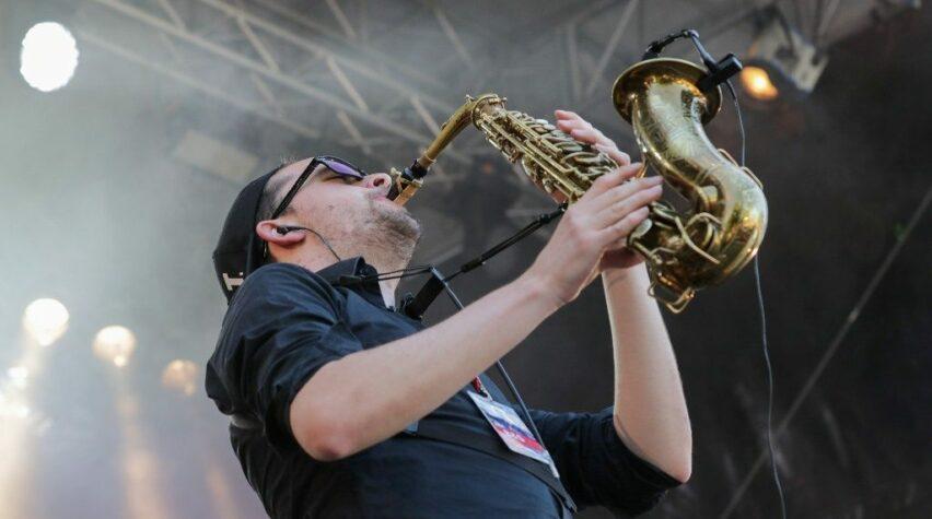 Fotografie eines Künstlers auf der Bühne mit Saxofon.