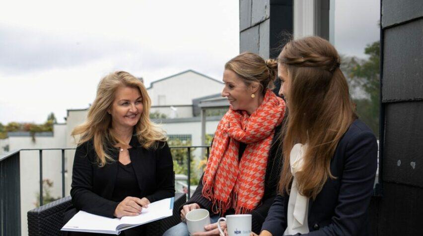 Drei Frauen sitzen auf einem Balkon mit Notizbuch und Kaffeetassen in der Hand.