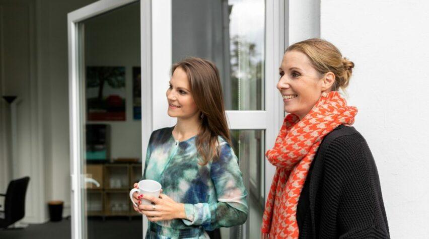 Zwei Frauen stehen seitlich zur Kamera vor einer geoeffneten Glastuer.