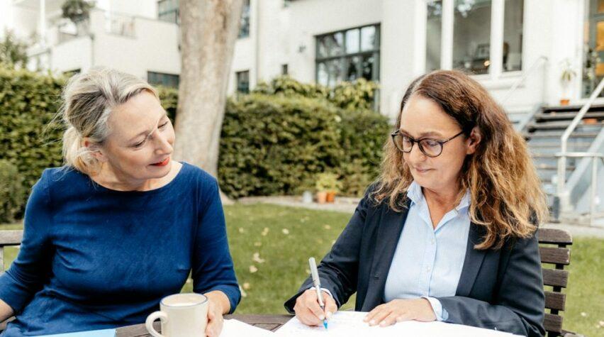 Zwei Frauen sitzen an einem Tisch im Garten und schreiben in ein offenes Buch.