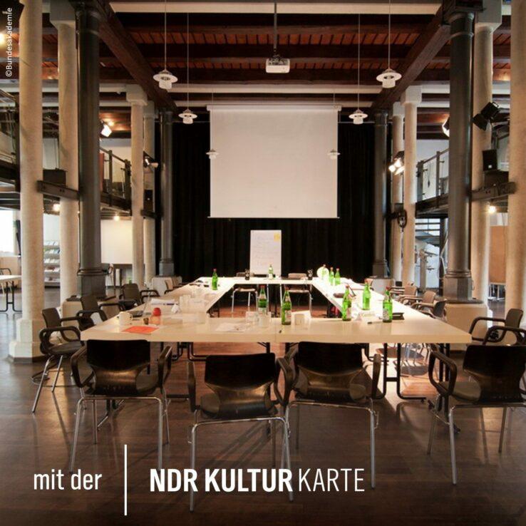 """Ansicht eines Konferenzraums, über den Konferenztisch hinweg Richtung Leinwand. Schrift: """"Mit der NDR Kultur Karte"""""""