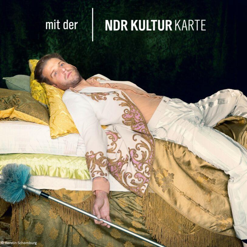 Ein Schauspieler extravangant auf einem Bett, in der Hand ein Staubwedel. Schauspiel Hannover
