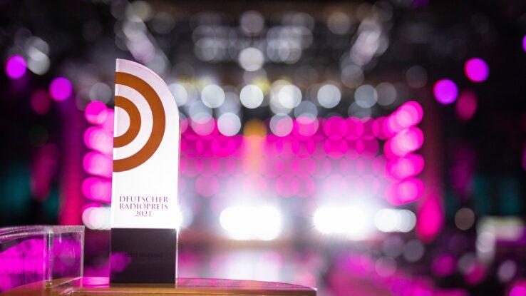 Die Auszeichnung Deutscher Radiopreis vor pinkem Hintergrund.